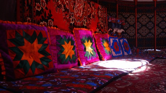 Cushions and tyshyks line the walls of a yurt